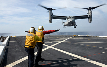 2 men in a flight crew signaling to an MV-22 landing
