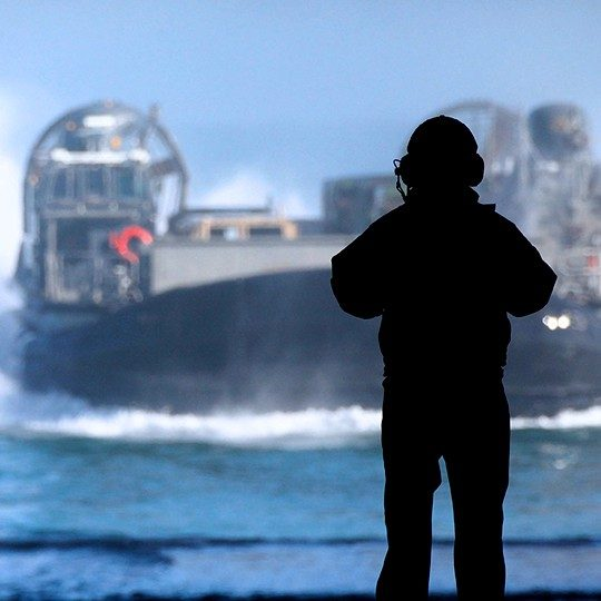 Silhouette of a sailor with a headset using maritime communications to communicate with a LCACs out at sea