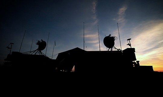 Silhouette of a military building at night with satellite communication equipment on the roof