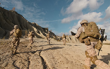 Warfighters running up a dirt hill