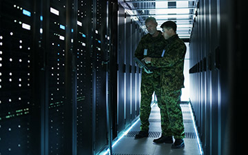 Two male warfighters utilizing defense technology looking at server racks