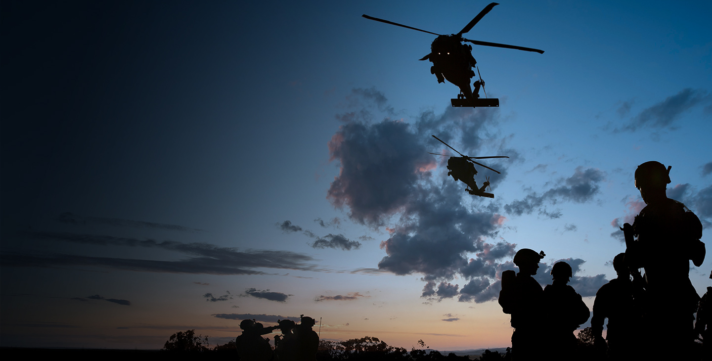 Rotary wing aircraft flying over soldiers utilizing defense technology at dusk