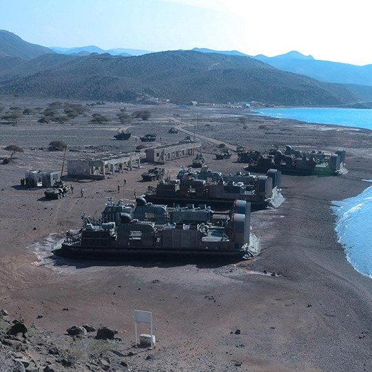 Military base with expeditionary vehicles utilizing defense communications