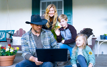 A rancher, his wife and 2 children enjoying home wifi outside on the porch with their laptop