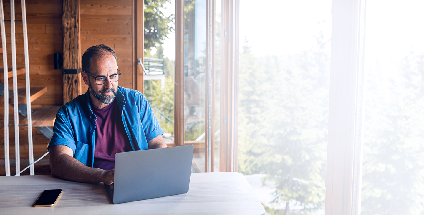 Man with a home wifi plan sitting at a table in his mountain house on a laptop