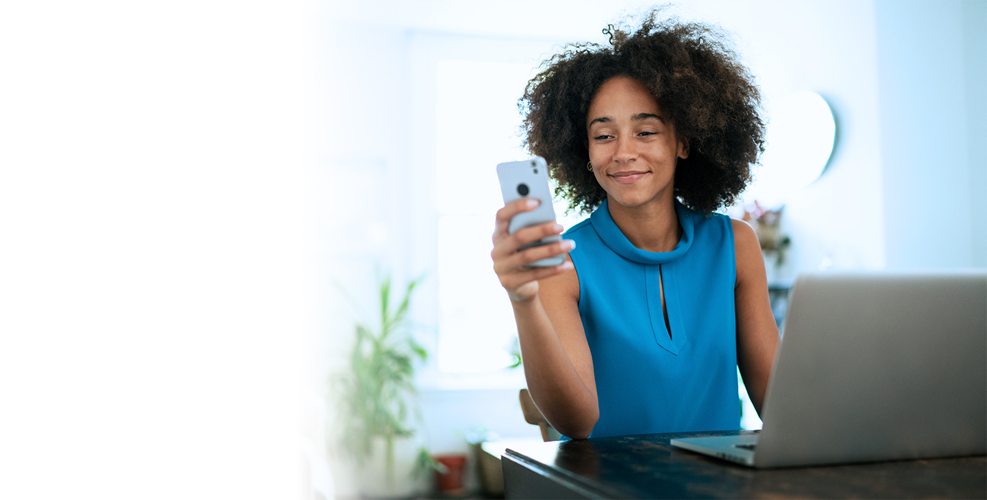 Woman in blue shirt, smiling and looking at her phone in front of a laptop, enjoying Viasat's internet packages