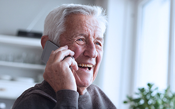Older man talking on a cell phone in his home utilizing VoIP, a Viasat internet add-on