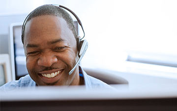 A customer support representative discussing internet packages wtih a customer on a headset, sitting behind a computer