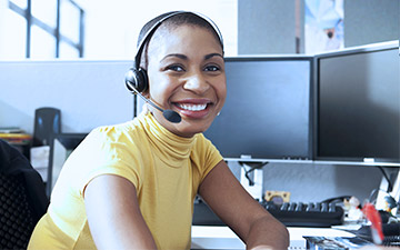 Female sales agent wearing a yellow shirt and headset, smiling at the camera