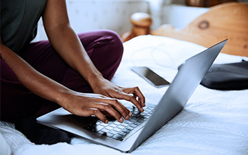 Close-up of a person sitting cross-legged on a bed typing on a laptop