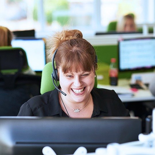 A woman working in a sales call center is smiling, talking to a customer about Viasat EasyCare