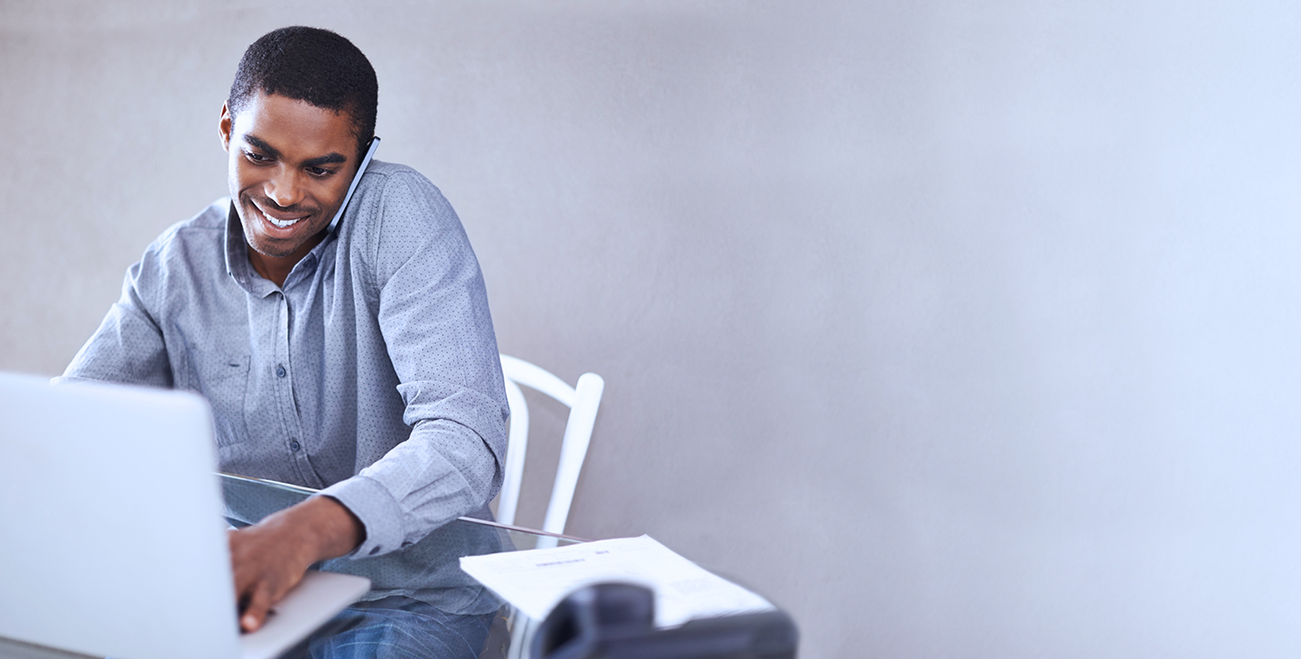 A man with Viasat's EasyCare sits on a white chair in front of a glass table, talking on the phone and using his laptop