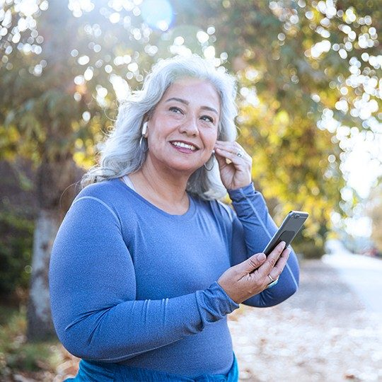 A woman standing outside with Apple earbuds talking on home VoIP service in front of a tree
