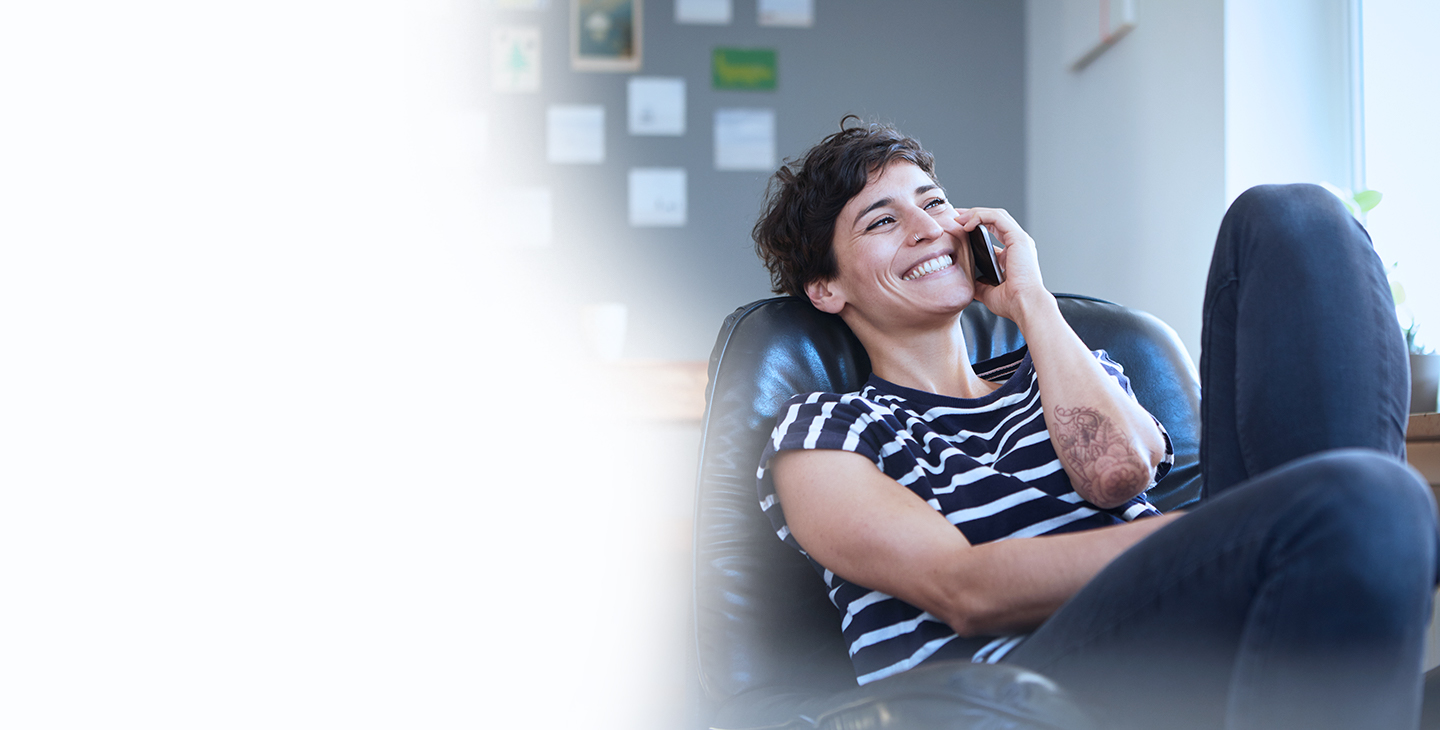 A woman with short dark hair and a striped shirt using VoIP home phone service