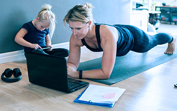 A woman in exercise clothes is planking on a mat while working on a laptop while her daughter sits next to her on a smartphone