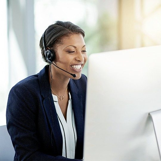 Woman in suit on Viasat support team telling a customer that WildBlue internet is now Viasat.