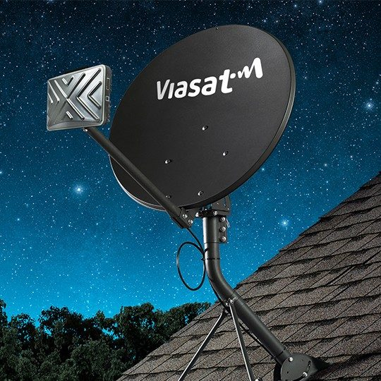 Gray fixed broadband terminal with TRIA and a white Viasat logo, mounted to the roof of a house against a starry night sky
