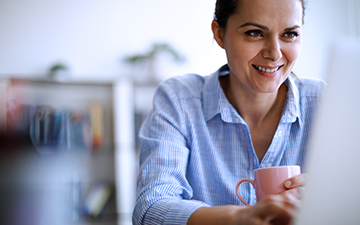 Woman sitting in front of her computer, drinking coffee and smiling