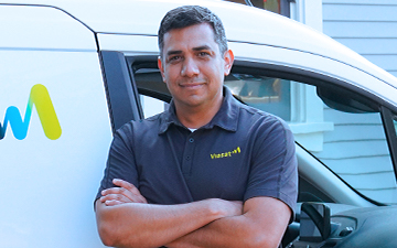 A Viasat installer stands in front of a white Viasat van with his arms crossed