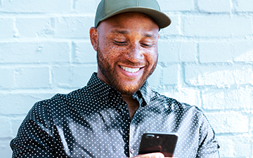 A man in a hat is smiling, looking at his smartphone