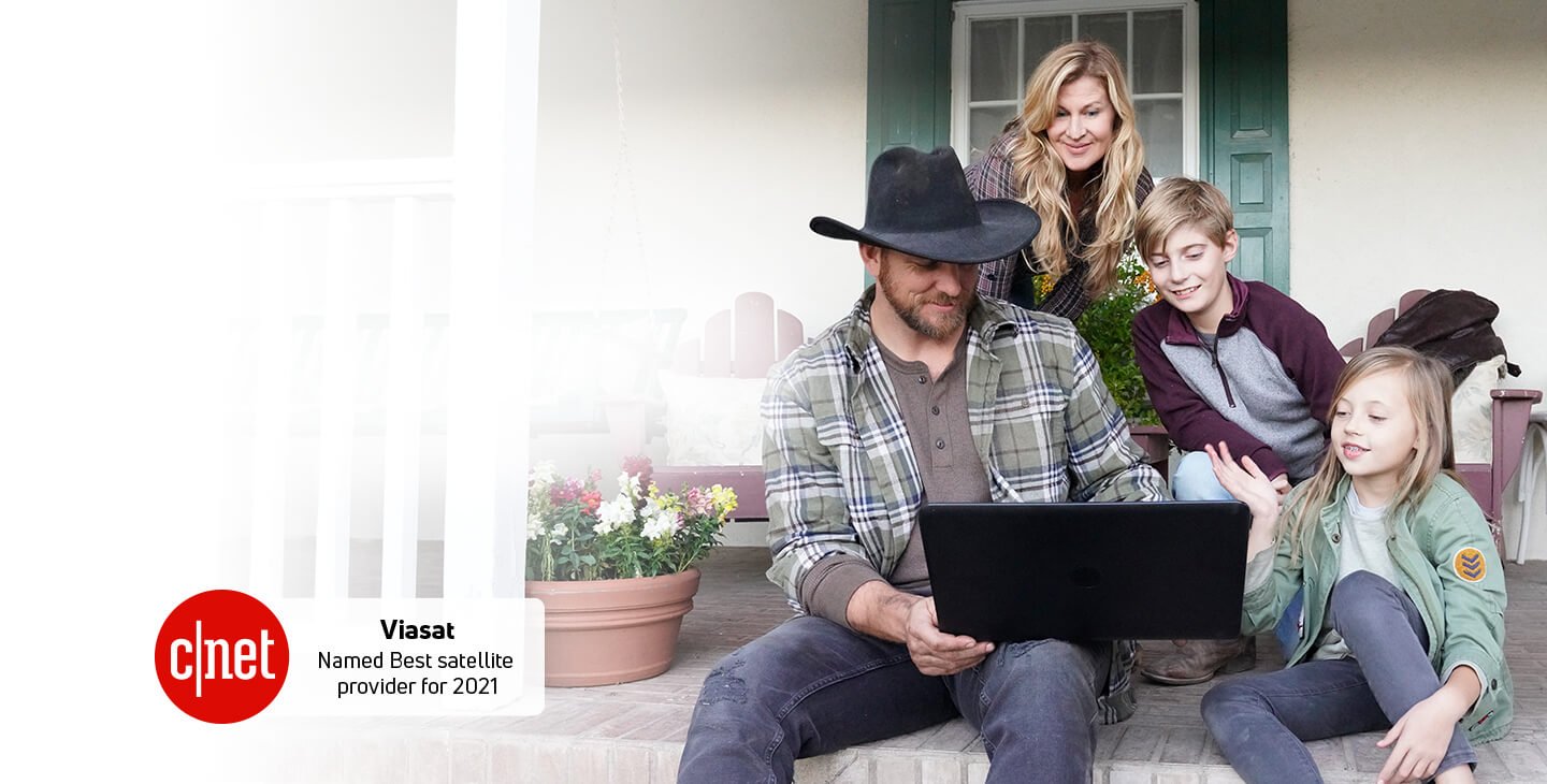 A rural family sitting on the front porch, using Viasat's satellite internet service on a laptop