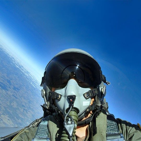 Fighter pilot looking out window of jet